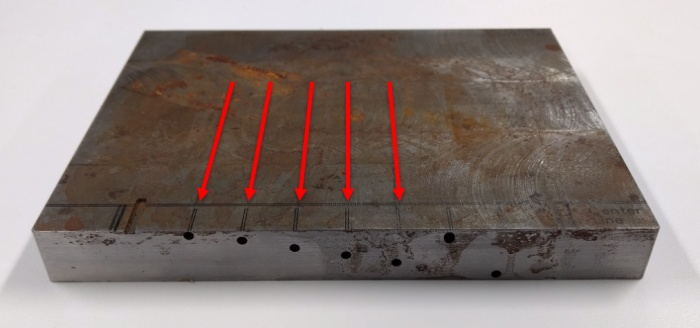 Custom-machined FBH test block showing the scan axes